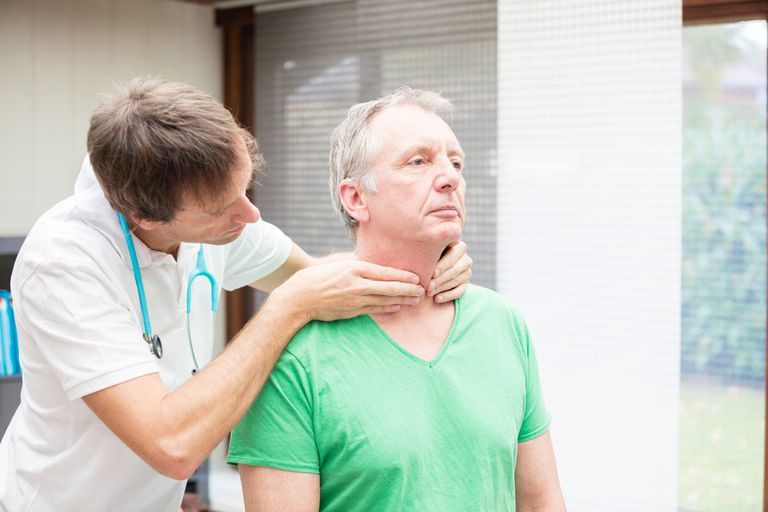 Doctor checking thyroid of patient