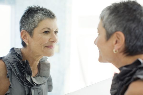 mature woman smiling in mirror