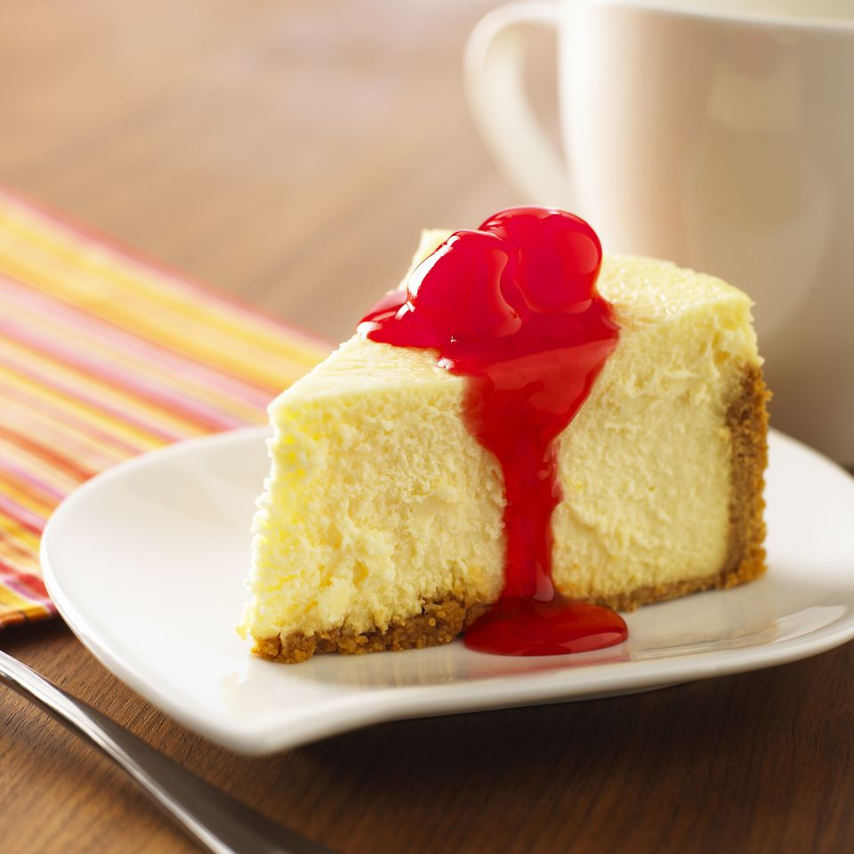 Slice of cheesecake with cherry topping on plate, close-up