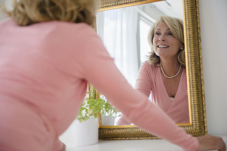 Caucasian woman admiring herself in mirror