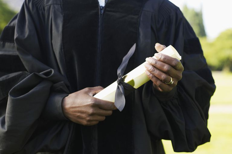 Mature woman in graduation gown holding diploma, mid section