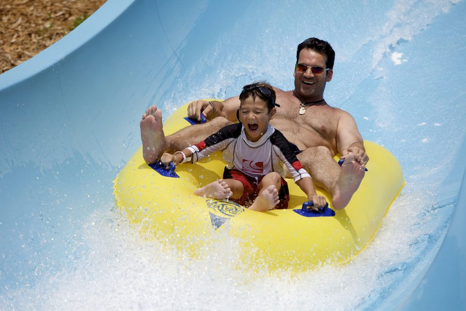 Man and son going down a water slide