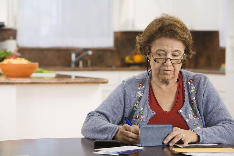 Woman writing checks in kitchen