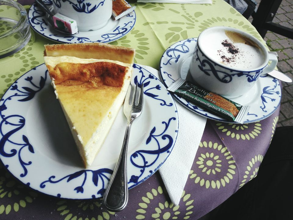 Cup Of Cappuccino And Slice Of Cheesecake On Sidewalk Cafe Table