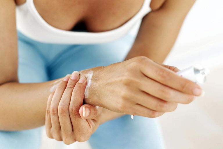 Woman rubbing ointment on her wrist