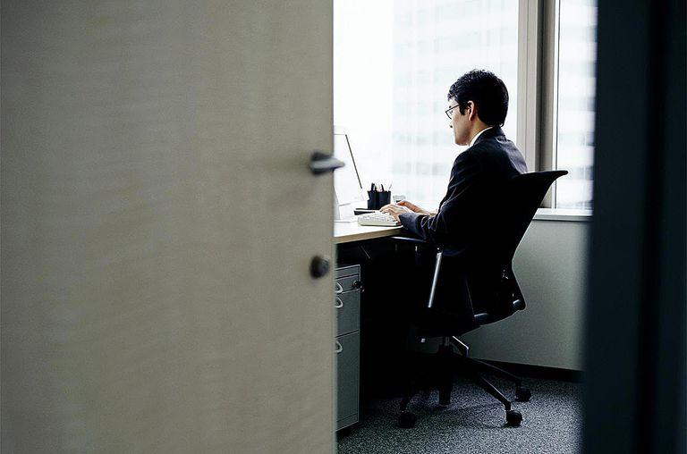 Businessman working on computer at desk in office, view through door