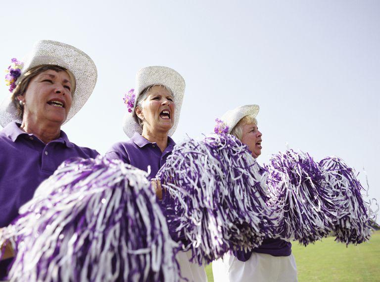 Three senior women in cheerleading uniforms cheering
