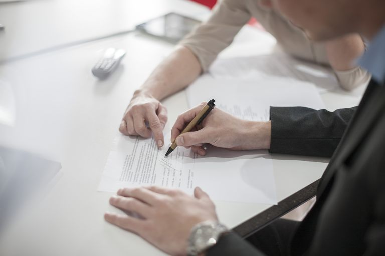 Close-up of man signing a document