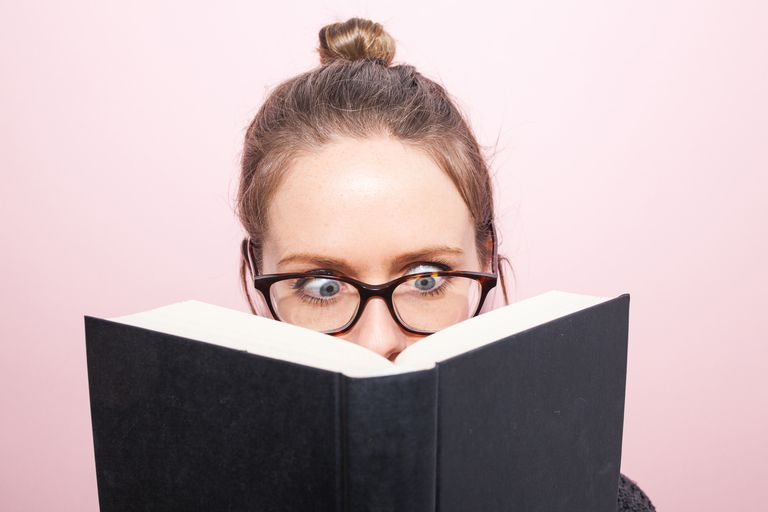 Young woman wearing glasses reading a book looking surprised