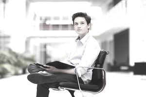 Teenage boy sitting in office chair, looking away