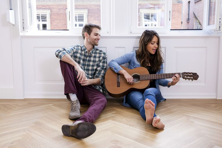 Young woman playing guitar with man