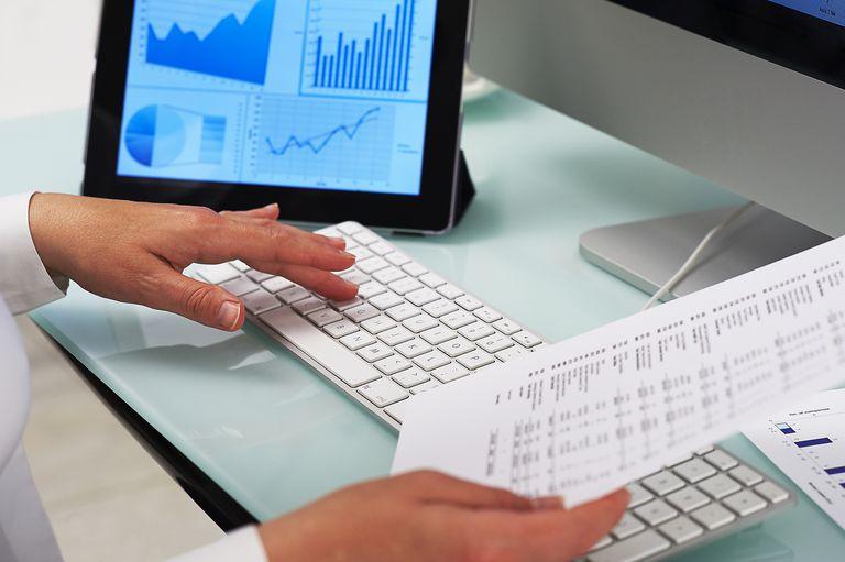man at desk looking at stocks on tablet