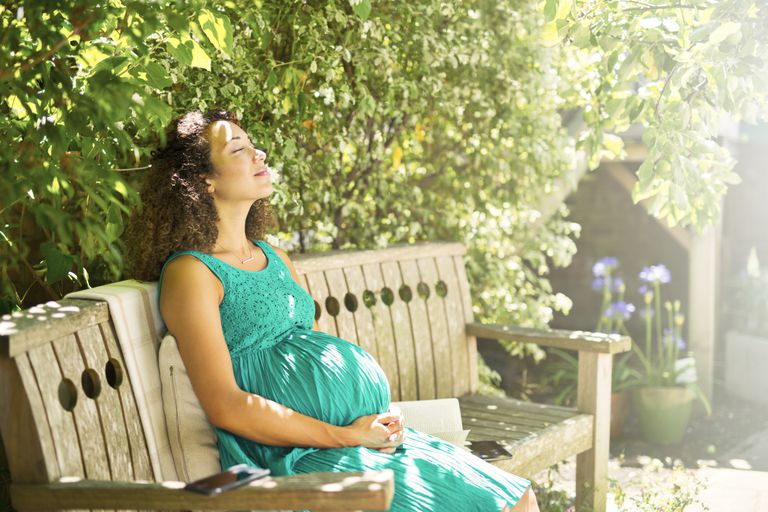 Pregnant woman sitting in the sun