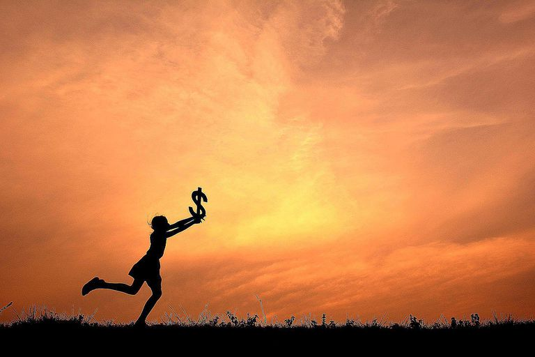 A girl chases a dollar sign through a field, symbolizing the way we are socialized to pursue economic success within the rules and norms of the system, an example of how cultural hegemony works.
