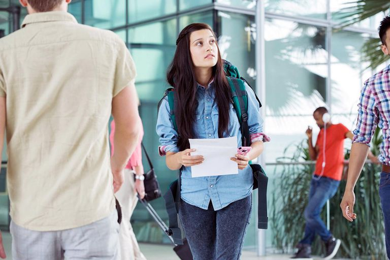 young woman with a piece of paper in her hands looking around for something