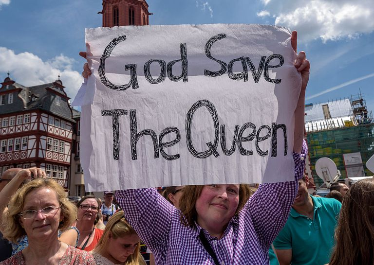 """Woman holding sign reading """"God Save the Queen"""""""