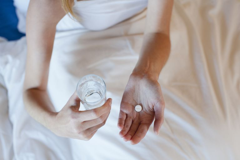 Woman with pill and water in hand