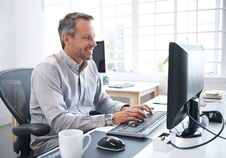 Portrait of a mature man working online in his office