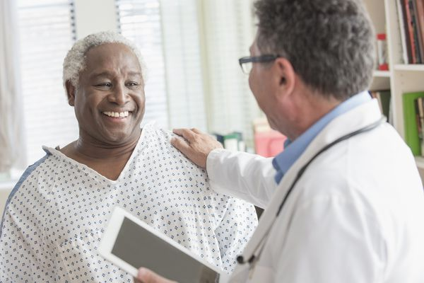 Doctor with digital tablet comforting older man in hospital