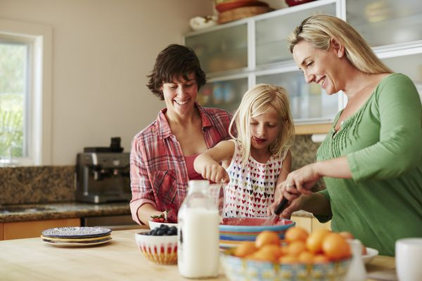 A same-sex couple is cooking with their kid.