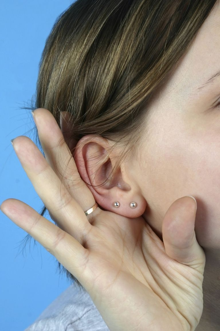 A woman with two piercings in her ear.