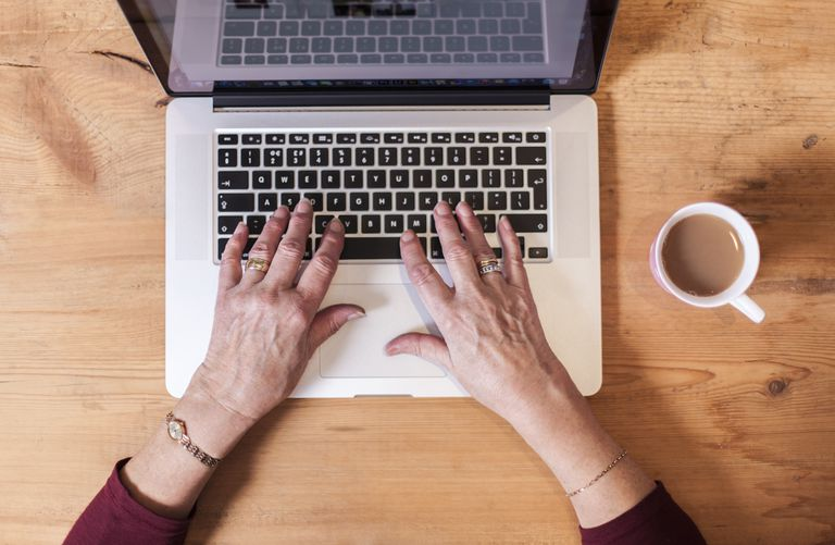Senior woman using laptop, focus on hands