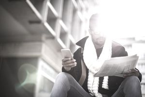 Businessman reading newspaper and using smartphone