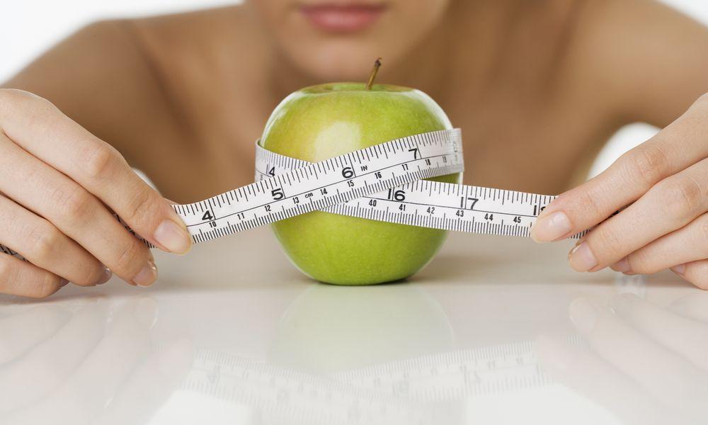 Woman measuring an apple