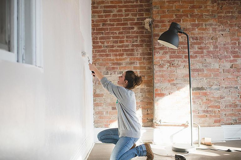 Young woman decorating with a paint roller in sunlight