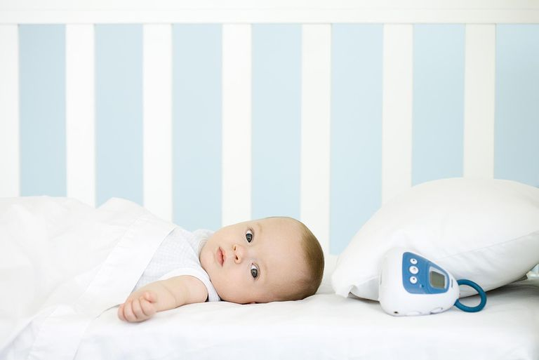 Infant lying in crib, looking at camera