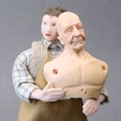A teen age doll in 1:12 scale holds the torso of a senior male doll in the same scale.