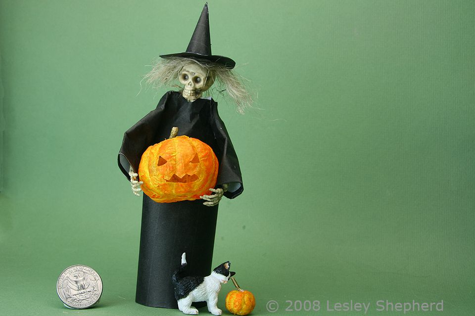 Dolls house scale skelton dressed as a witch, holding a carved paper mache pumpkin.
