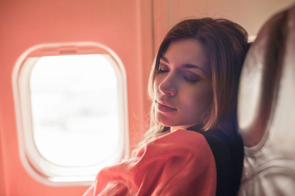 Female passenger asleep under blanket on airplane