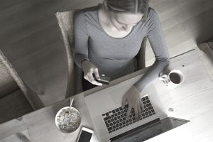 Woman using credit card at computer