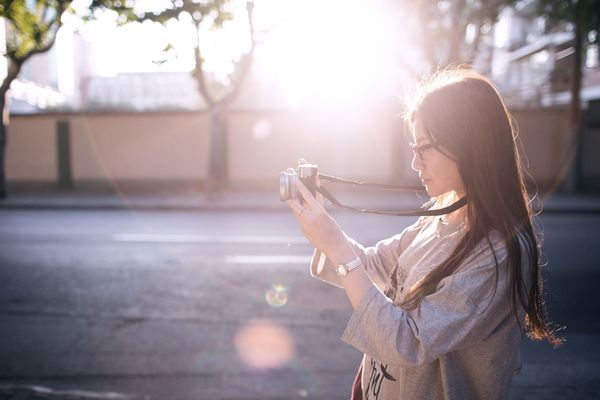 Young Asia girl taking pictures under backlight