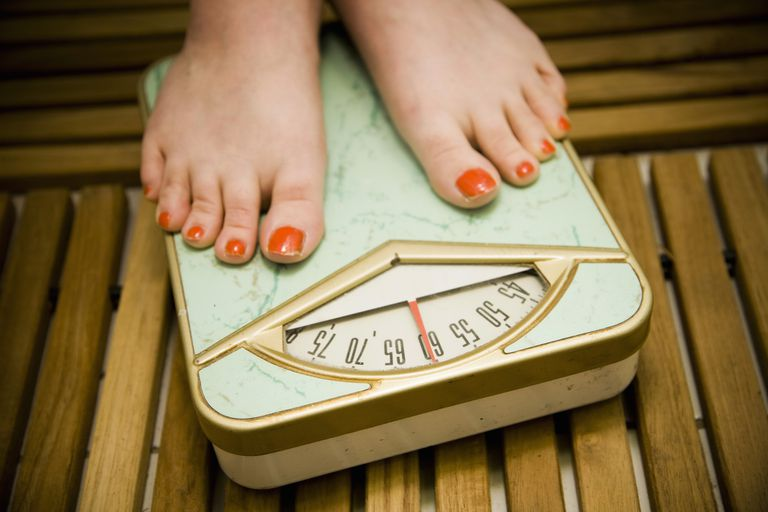 Woman with painted toenails standing on a scale