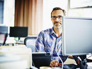 Smiling mature businessman sitting at workstation