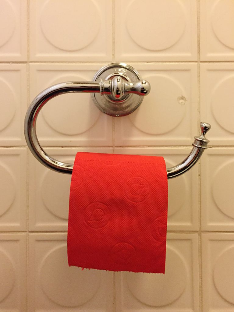 Close-Up Of Red Toilet Roll On Wall In Bathroom