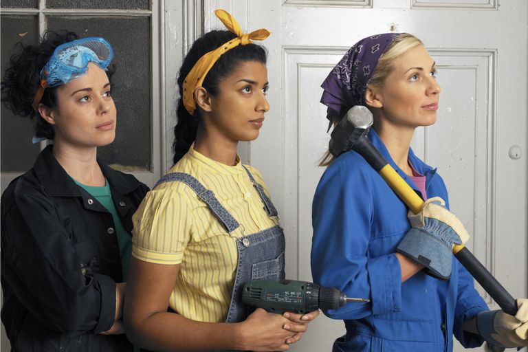 Three young women wearing overalls standing in a row