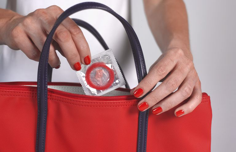 Woman taking a condom from her purse