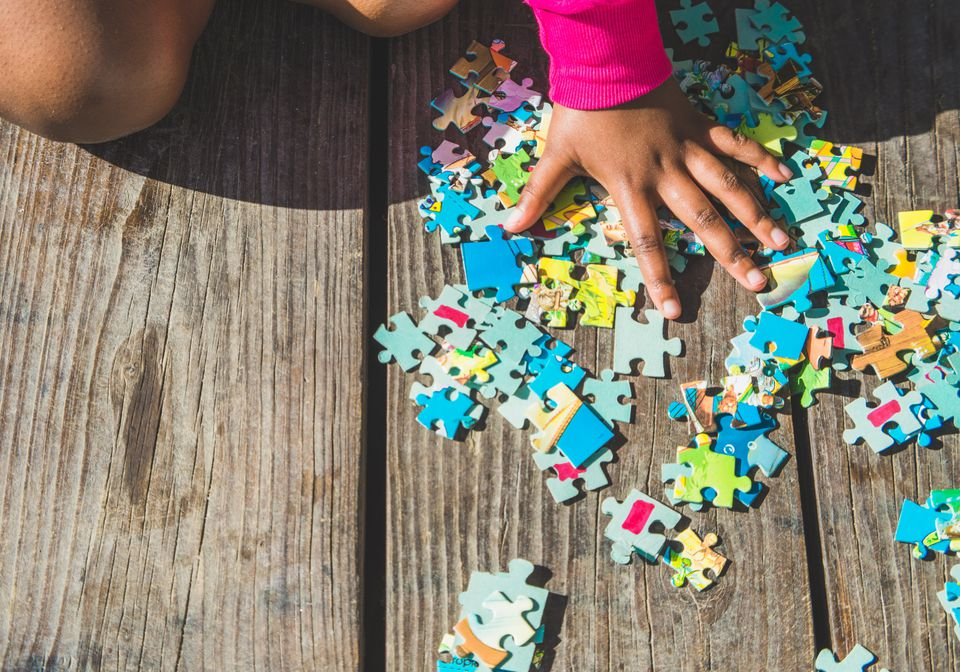 Child Sorting Puzzle Pieces On Wooden Deck