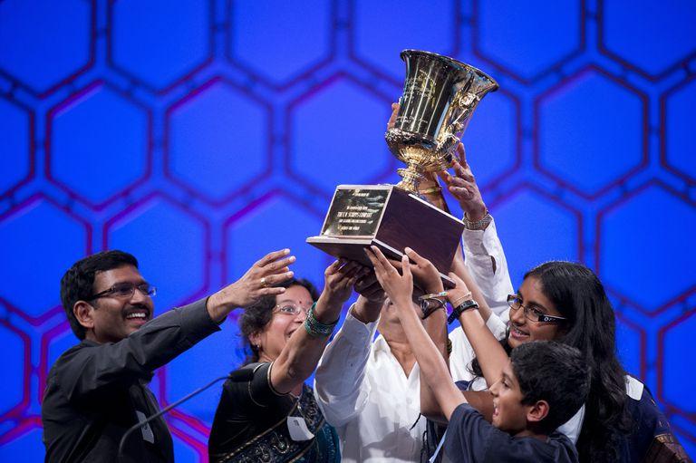 Kids holding spelling bee trophy