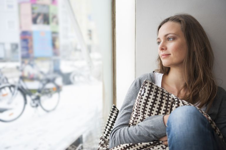 woman daydreaming while looking out window