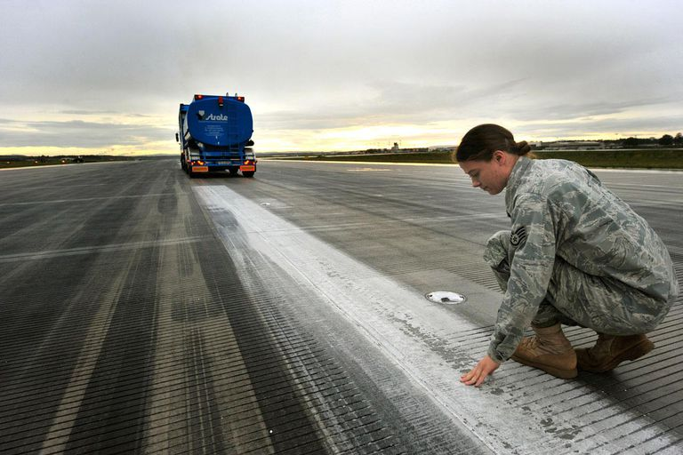 Staff Sgt. Stephanie Heck checks the amount of rubber and paint removed from the runway after a truck equipped with a high-powered pressure washer makes its first pass, July 19, 2011, at Ramstein Air Base, Germany. Sergeant Heck is the NCO in charge of the airfield management operations section.
