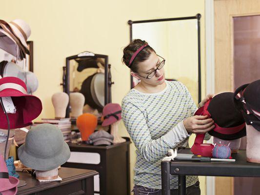 Shop assistant checks trim on hat