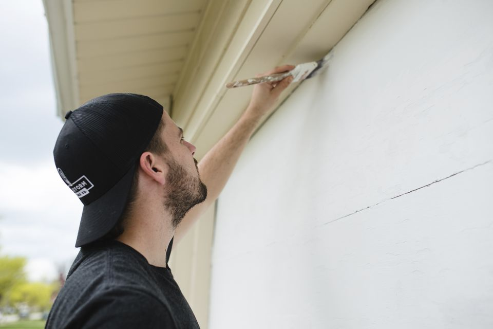 Side view of bearded man wearing baseball cap painting outside of a house.
