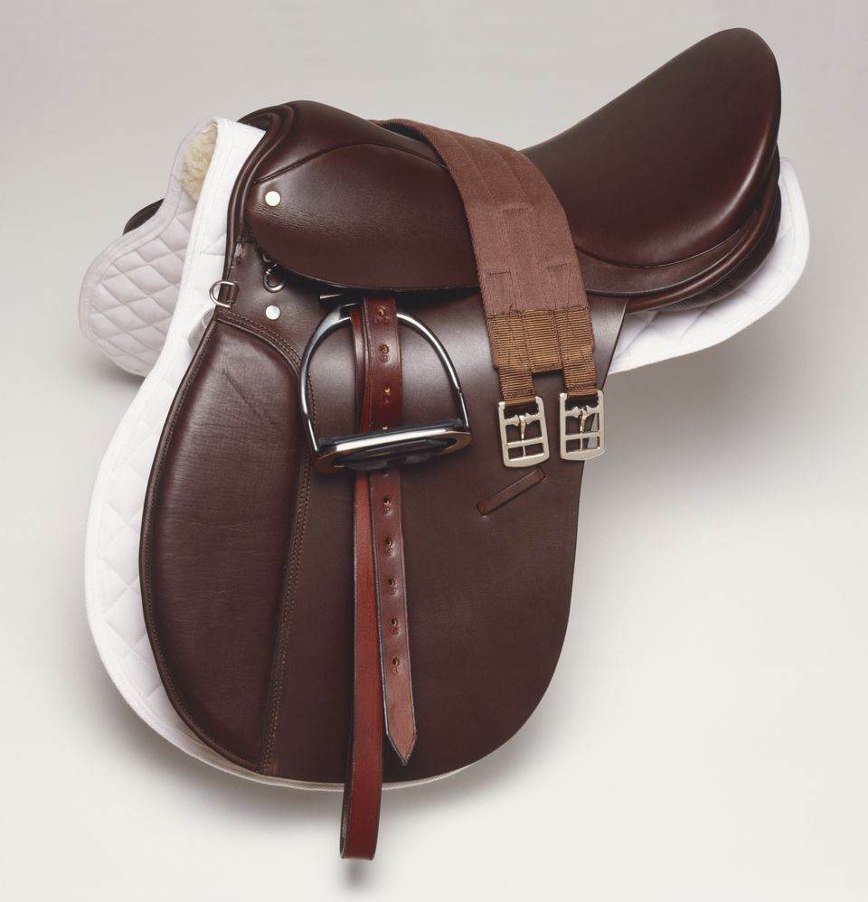 Brown leather horse riding saddle, side view.