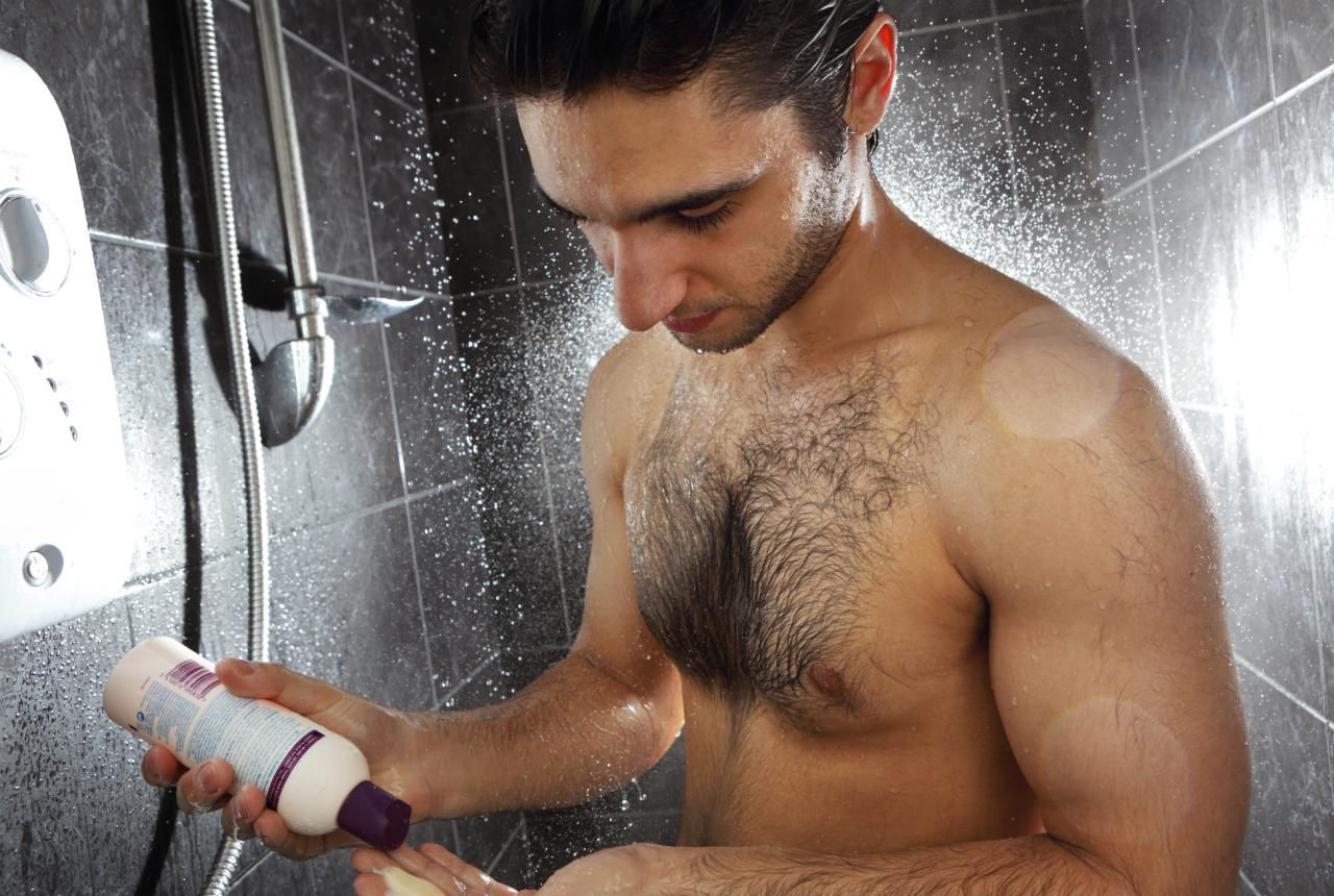 Sexy man taking shower clothing on stock photo