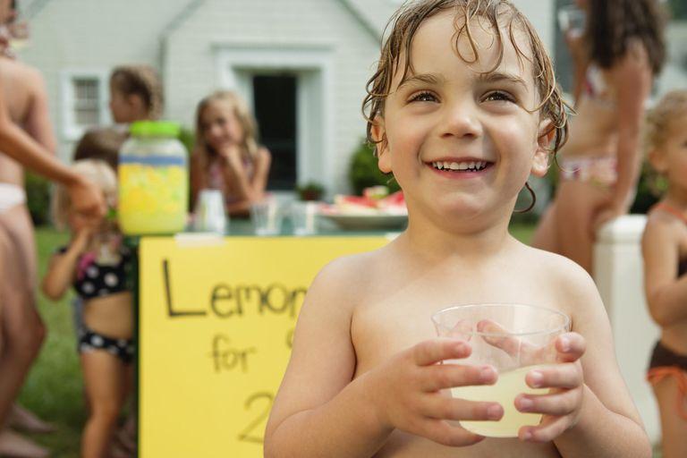 Little boy holding glass in front of lemonade