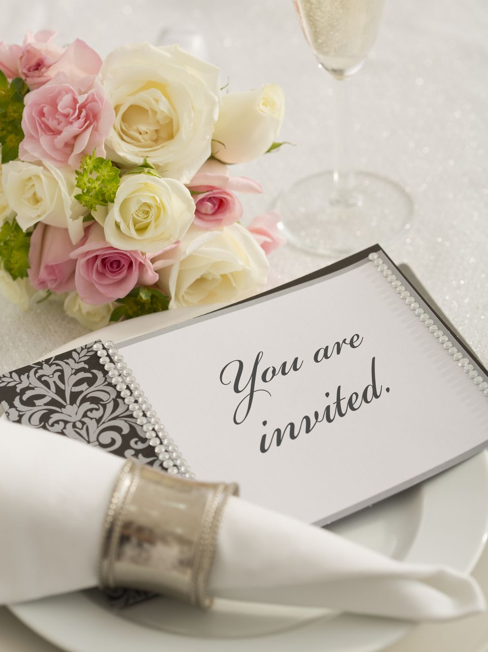 wedding invitation on a dinner plate with bouquet